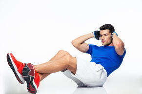 Fitness man doing abdominal exercises isolated on a white background