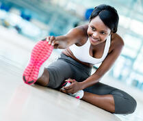 Gym woman stretching her leg for warm-up